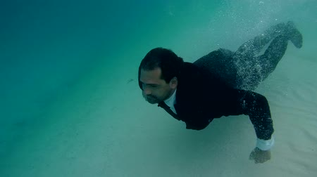podwodny swiat : A man in a wedding suit dives under water of the Indian Ocean, Maldives