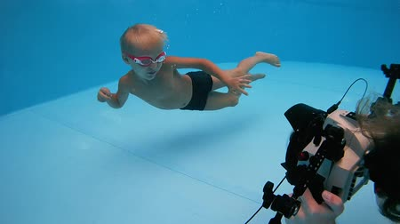 kiddy : Boy in goggles swimming underwater and posing for underwater photography in the pool