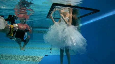 kiddy : girl in short, white dresses wearing poses underwater in swimming pool