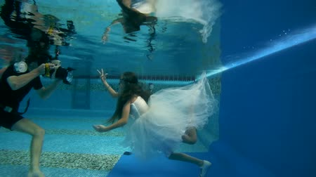 fényképész : girl in short, white dresses wearing poses underwater in swimming pool