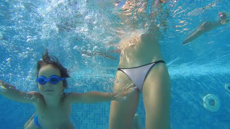 kiddy : Mom teaches a little boy in swimming goggles playing under water in the swimming pool