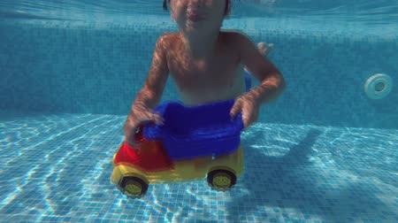 kiddy : A little boy playing under water in the swimming pool