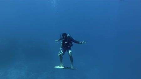 текущий : Scuba diver skates in a current standing on the fins as a surfboard, Indian Ocean, Maldives