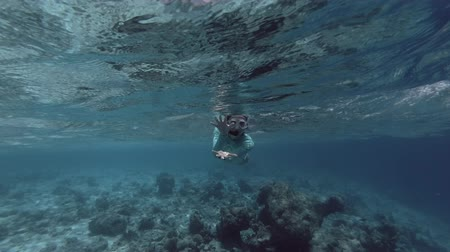 snorkeling : Young beautiful woman floats in the mask and fins floats on the surface of the blue water and depicts a shark attack (underwater view), Indian Ocean, Maldives Stock Footage