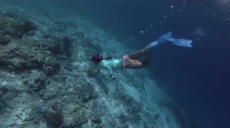 potápěč : Young beautiful woman in a mask and fins dives underwater to a coral reef, Indian Ocean, Maldives