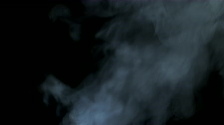 magia : White steam rises diagonally blowing from bottom to top on black background.