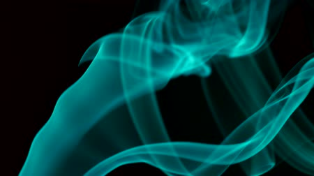 flexionar : Thin trickle of bright turquoise smoke blowing from bottom to top. Closeup
