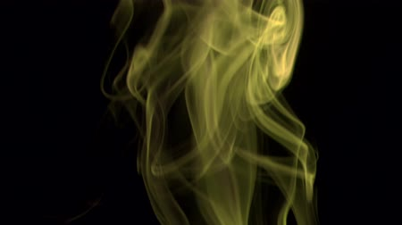 black yellow : Bright yellow smoke, isolated on black background. Closeup.