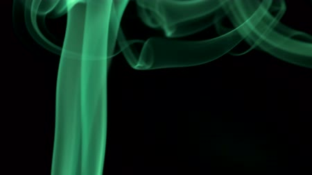 lebeg : Green smoke twists to top on black background. Closeup