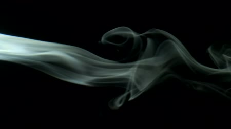 upward : Vertical video screensaver - trickle silvery smoke slowly rising graceful twists upward. Cigar smoke blowing from the left side. Closeup, isolated on black background.