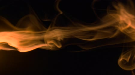 upward movement : Vertical video screensaver - Thin trickle golden smoke slowly rising graceful twists upward. Colored smoke blowing from the left side. Closeup, isolated on black background.