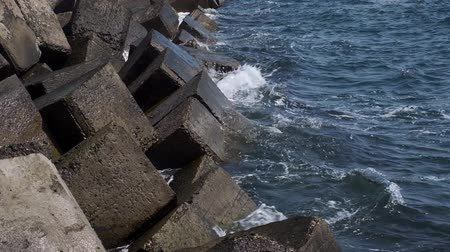 vasalás : Destroyed coastal concrete protective structure. Large deep cracks from erosion of impact of sea wave. Close-up, Full HD - 60fps Stock mozgókép