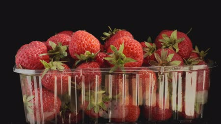 ovocný : Rotation of juicy ripe strawberries in disposable plastic box on black background. Rotation 360 degrees, closeup. 4K - 50fps