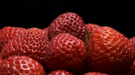 fruity garden : Red strawberries on a black background. Close-up, Camera rotation 360 degrees. Stock Footage