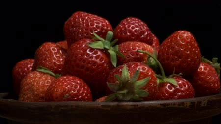 fruity garden : Rotation of juicy ripe strawberries on black background. Rotation 360 degrees, closeup. 4K - 50fps