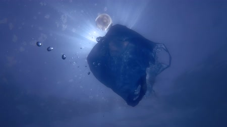 Blue plastic bag swims underwater. Underwater shot, Low-angle shot, backlight
