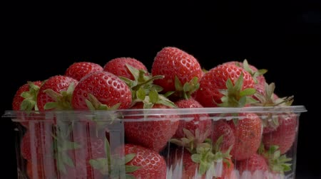 Juicy ripe strawberries in disposable plastic food pack on black background. Rotation 360 degrees, closeup Dostupné videozáznamy
