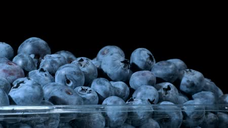dairesel : Fresh blueberries in disposable plastic food pack on black background. Close-up, Camera rotation 360 degrees. Bog bilberry, bog blueberry, bilberry or western blueberry (Vaccinium uliginosum) Stok Video