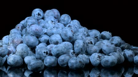fruity garden : Rotate of blueberries on black glass with reflection. Close-up, Camera rotation 360 degrees. Bog bilberry, bog blueberry, bilberry or western blueberry (Vaccinium uliginosum) Stock Footage