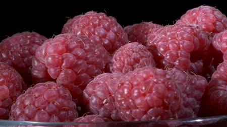 Rotate of fresh raspberries in glassware on black background. Close-up, Camera rotation 360 degrees. European raspberry or red raspberry (Rubus idaeus) Stockvideo