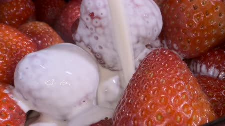 fruity garden : Cream pours on fresh strawberries. Close-up.