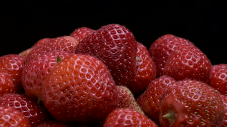 fruity garden : Slow motion rotation of fresh strawberries on black background. Close-up, Camera rotation 360 degrees. Stock Footage