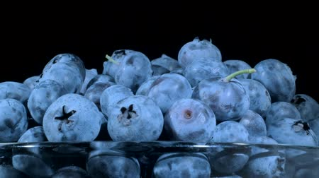cristaleria : Fresh blueberries in glassware on black background. Close-up, Camera rotation 360 degrees. Bog bilberry, bog blueberry, bilberry or western blueberry (Vaccinium uliginosum)