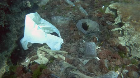 poluir : Slow motion, Massive plastic pollution of the ocean bottom. Tropical fishes slowly swims over the bottom covered with a lot of plastic garbage. Plastic debris on the seabed in Mediterranean Sea