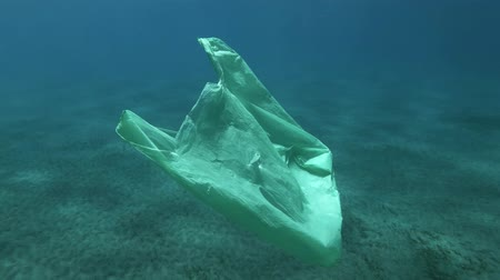 poluir : Slow motion, old green plastic bag bag drifts slowly under surface in blue water. Underwater plastic pollution of the oceans. Plastic garbage environmental pollution problem Stock Footage