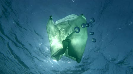 podsvícení : Slow Motion, Green plastic bag slowly drifting underwater surface in the sunrays. Plastic pollution of the ocean. Underwater shot, Low-angle shot, Contre-jour (backlighting).