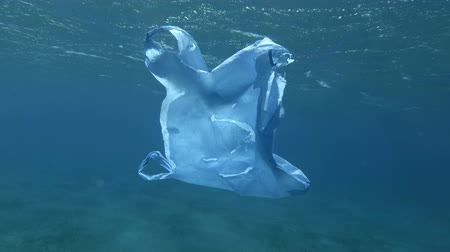 oceány : Slow motion, old bllue plastic bag drifts slowly under surface in blue water. Underwater plastic pollution of the oceans. Plastic garbage environmental pollution problem Dostupné videozáznamy