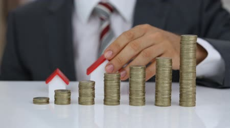 ипотека : Businessman Protecting And Arranging Different Type Of House Model Behind The Rising Stack Of Coins