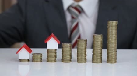 Businessman Protecting And Arranging House Model On The Rising Stack Of Coins