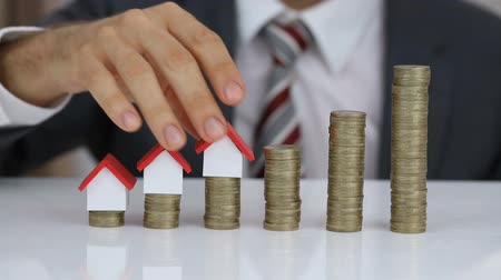 real : Close-up Of A Businessman Arranging The House Model On The Rising Stack Of Coins Stock Footage