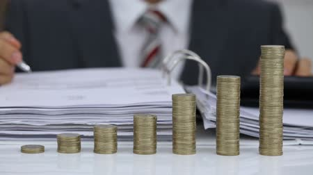 Close-up Of A Businessman Calculating Financial Expenses Using Calculator In Front Of Coins Stack Wideo