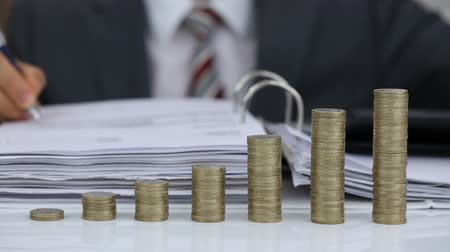 Close-up Of A Businessman Putting Coins On Rising Coins Stack After Calculating Expenses