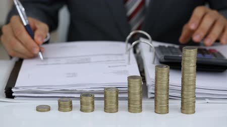Close-up Of A Businessman Calculating Financial Expenses Using Calculator With Coins Stack On Desk Wideo