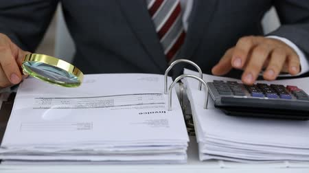 Close-up Of A Businessman Holding Magnifying Glass Calculating Invoices Using Calculator Stock Footage