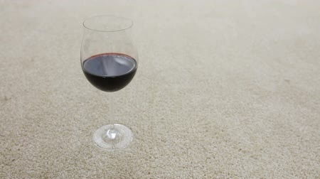 Close-up Of A Persons Hand Falling A Glass Of Red Wine On Carpet