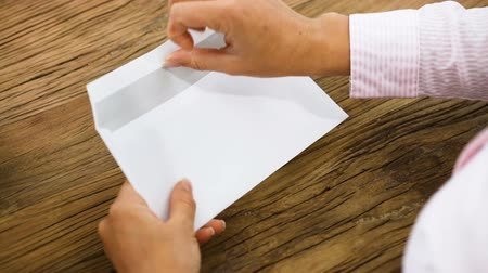 Businesswoman Removing A You Are Getting Audited Card From Envelope On Office Desk