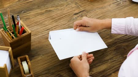 Elevated View Of A Businessperson Opening An Invoice From White Envelope On Office Desk Wideo