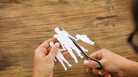 Close-up Of A Person Cutting The Paper Cut Out Family With Scissors On Desk