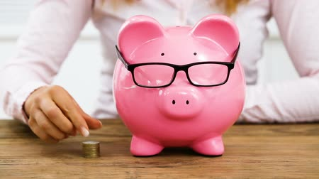 Businesswoman Inserting Coins In Pink Piggy Bank With Glasses On The Wooden Desk Wideo