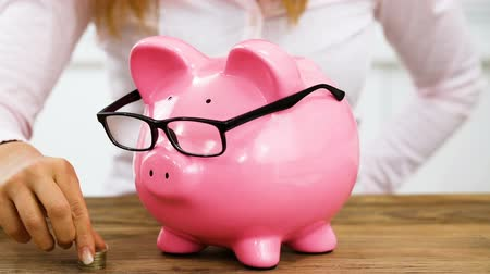 A Businesswoman Saving Money By Inserting Coins In Piggy Bank With Glasses On Wooden Desk