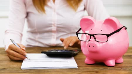 Close-up Of A Businesswoman Calculating Invoice With Calculator In Front Of Piggy Bank On Desk