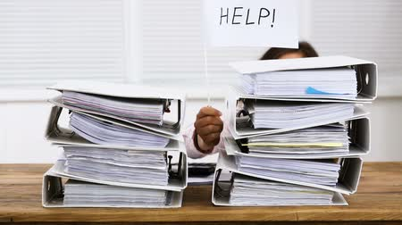 Stack Of Folders In Front Of A Businesswoman Holding White Flag With Help Text