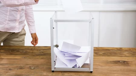 Close-up Of A Persons Hand Inserting Vote In Ballot Box On Wooden Desk