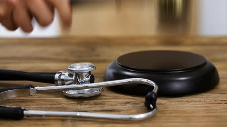 Close-up Of A Judge Hitting Gavel On Mallet With Stethoscope On Desk In Courtroom Wideo