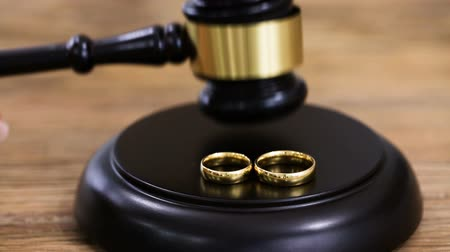 Close-up Of A Person Hitting Gavel With Golden Wedding Rings On Mallet At Desk Wideo