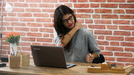 Young Woman With Neck Pain Sitting At Office Desk Using Laptop